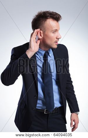 young business man listening with his hand behind his ear. on a light gray studio background