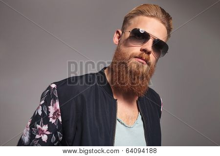 portrait of a casual young man with a long red beard looking into the camera. on gray studio background