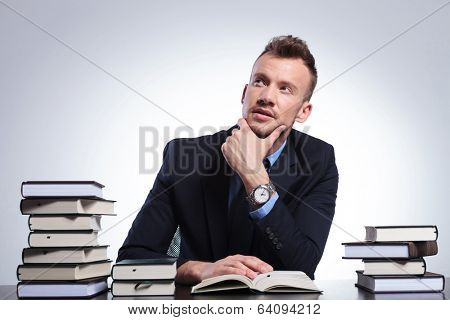 young business man at his office reading a book and thinking while looking up with his hand at his chin. on a light studio background
