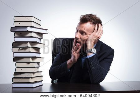 young business man sitting at his desk and looking with his hand at his mouth at a big stack of books. on a light studio background