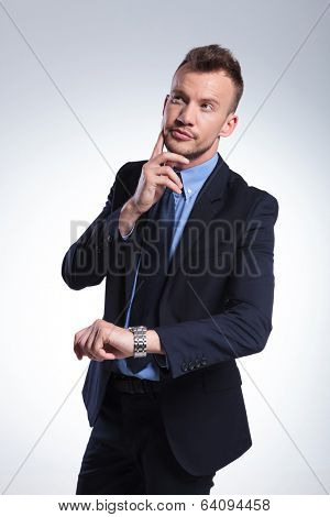 young business man pondering about the time while holding his hand at his cheek and looking away from the camera. on a light gray studio backgroud
