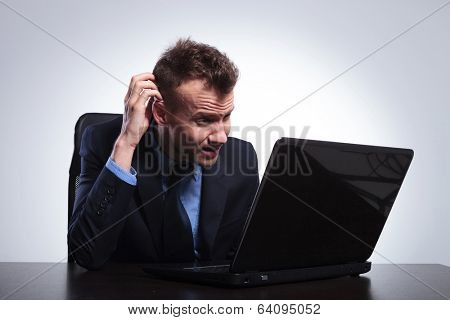 young business man reading something on his laptop and not understanding, scratching his head. on a gray studio backgroud