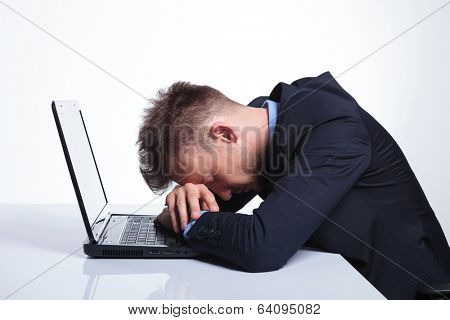 young business man taking a nap with his head in his laptop, over his hands. on a gray studio backgroud