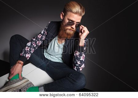 young bearded man looking over his sunglasses while sitting with his feet together. on a black studio background