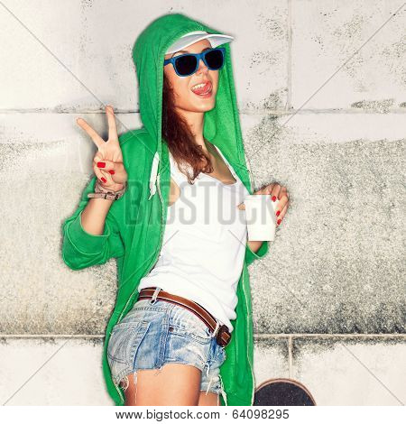 Beautiful Lady In Jeans Shorts With Skateboard Against  Grey Wall