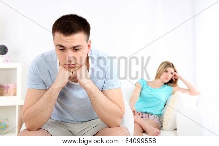 Portrait of young man and woman  conflict sitting on sofa argue unhappy, on home interior background