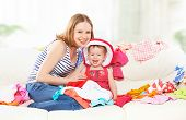 image of dowry  - Happy Mother and baby girl with clothes ready for traveling on vacation - JPG