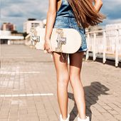 image of overalls  - back view of young girl in short overalls with long legs and long silky hair holding skateboard - JPG