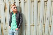 foto of long beard  - picture of a young casual redhead bearded man looking to his side while holding his hands in his front  pockets - JPG