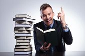 picture of understanding  - young business man reading at an office with a stack of books and pointing up with a smile on his face - JPG