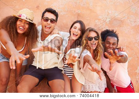 Group Of Friends On Holiday Together Posing By Wall