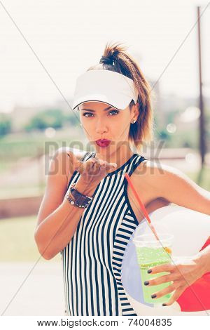 Sporty Woman Drinking Water Against The Sportsground