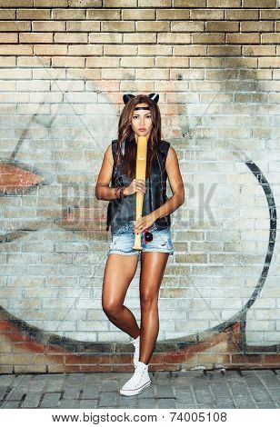 Bad girl with leather cat ears holding a baseball bat