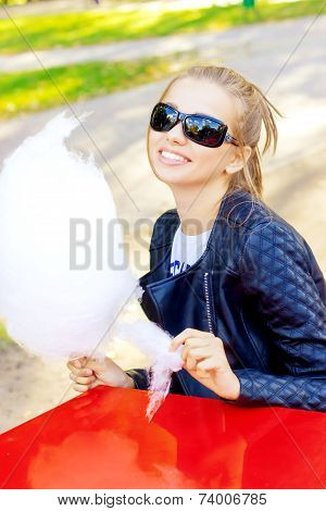 beautiful happy smiling girl sun glasses eating cotton candy at a table in the Park on a Sunny day