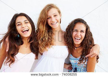 Portrait Of Three Teenage Girls Leaning Against Wall