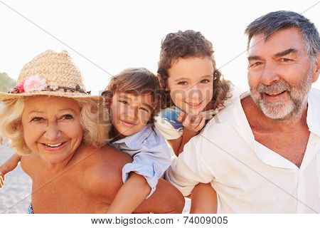 Grandparents Giving Grandchildren Piggybacks On Summer Holiday