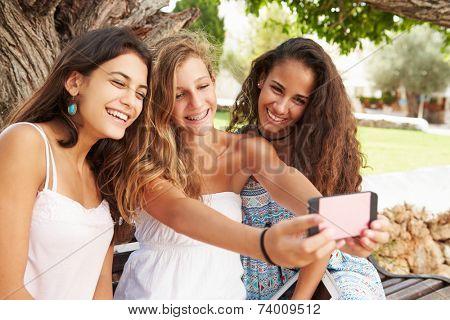 Three Teenage Girls Sitting On Bench Taking Selfie In Park