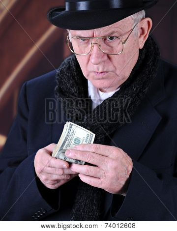 Close-up image of the miserly Mr. Scrooge looking up suspiciously while holding a fistful of 100 dollar bills.