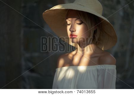 Beautiful young lady in straw hat in the palace