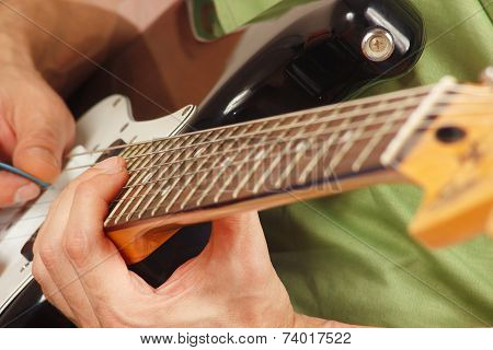 Rock musician put fingers for chords on electric guitar close up