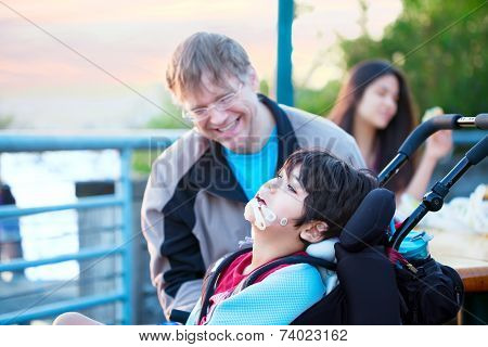 Father enjoying time outdoors with disabled son in wheelchair