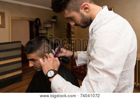 Male Hairdresser Cutting Hair Of Smiling Man Client