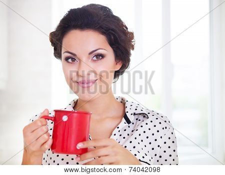 Happy Woman Holding A Cup Of Coffee Wearing Pajamas