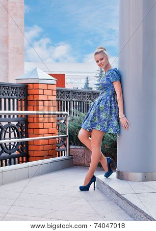 Young girl blonde in blue short dress