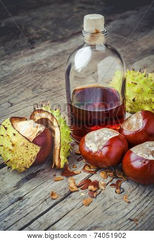 Chestnuts And Bottle With Tincture On Wooden Table