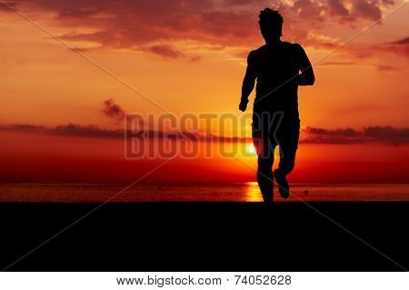 Perfect silhouette of fit man doing workout at early morning on the beach