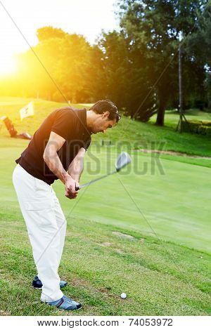 Professional golf player in action hitting golf ball at sunset