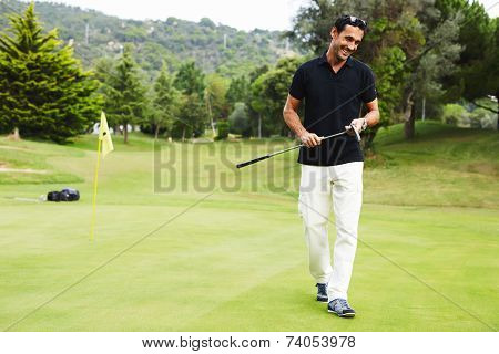 Golf player carrying his bag and walking on golf course