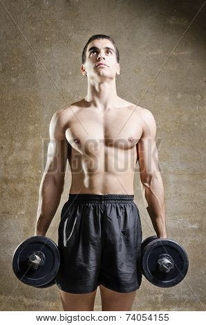 Young Man Training Weights In Old Gym
