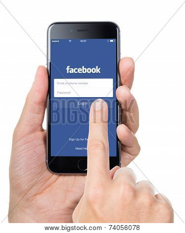 Hand Trying To Log In Facebook Application On Apple Iphone 6