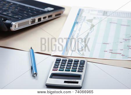 Calculator, pen,laptop, document lying on the desk