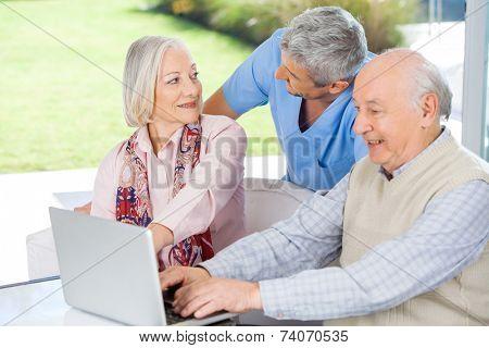 Male caretaker looking at senior woman by man using laptop at nursing home