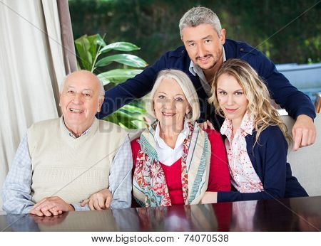 Portrait of happy couple with grandparents at nursing home