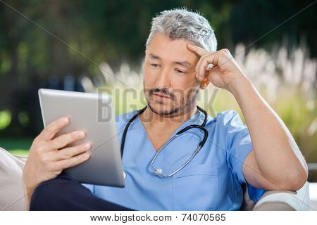 Male doctor using tablet PC in nursing home