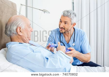 Male caretaker explaining prescription to senior man in bedroom at nursing home