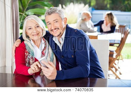 Portrait of smiling grandmother and grandson using smartphone with family in background at nursing home