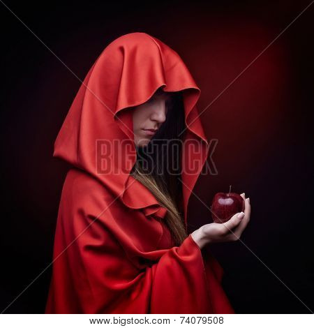 beautiful woman with red cloak holding apple - studio shot