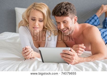 Close up Sexy Young Couple on White Bed Watching Movie on White Tablet. Captured on Gray Wall Background.