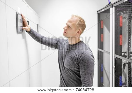 Engineer adjusts air conditioner in datacenter