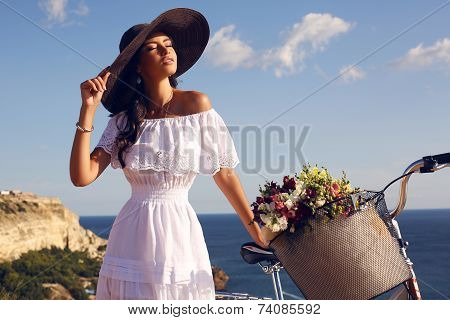Pretty Brunette In Elegant Dress And Hat Riding A Bicycle Along The Coast