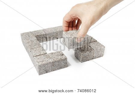 Man finishing a square made of small blocks of granite rock.