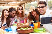 stock photo of lunch  - Group Of Friends Taking Selfie During Lunch Outdoors - JPG