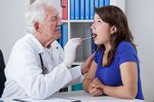 stock photo of pharyngitis  - General practitioner examining throat of young woman - JPG
