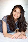 stock photo of biracial  - Beautiful biracial teen girl on formal dress lying down relaxing  - JPG