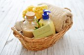 stock photo of pumice-stone  - Shower gel with olive soap and bath towels in basket on wooden background - JPG