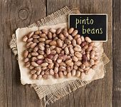 foto of pinto bean  - Pinto beans with small chalkboard on a wooden table - JPG
